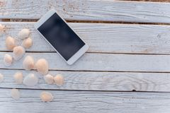 The smartphone lies in the encircling of seashells on wooden boards. stock photos