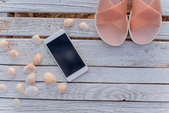 The smartphone lies in the encircling of seashells on wooden boards. royalty free stock photos