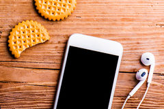 Smartphone, los auriculares y las galletas pusieron en el escritorio de oficina viejo foto de archivo