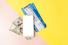Smartphone, lotniczy bilet i dolary na, pastelowych menchiach i koloru żółtego tle Minimalny styl, flatlay obraz stock