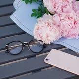 Smartphone, lunettes et bouquet des pivoines sur la table en bois dans le restaurant extérieur Espace de travail Datation, réunio Photos stock