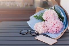Smartphone, lunettes et bouquet des pivoines sur la table en bois dans le restaurant extérieur Espace de travail Datation, réunio Photo stock