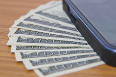 Smartphone lying on the United States dollars,. Close up on dollar bills, Smartphone lying on the United States dollars Stock Photo