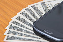 Smartphone lying on the United States dollars,. Close up on dollar bills, Smartphone lying on the United States dollars Royalty Free Stock Photos