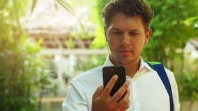 Smartphone man som utomhus använder den smarta telefonen för mobil cell i sommar stock video