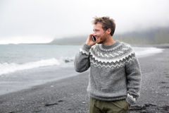 Smartphone man talking on phone on beach, Iceland. Smartphone man talking on smart phone walking on black sand beach on Iceland wearing Icelandic sweater Royalty Free Stock Photo