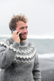 Smartphone man talking on phone on beach, Iceland. Smartphone man talking on smart phone walking on black sand beach on Iceland wearing Icelandic sweater by the Stock Photo
