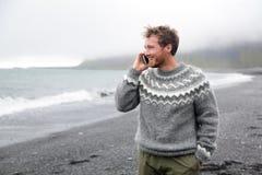 Smartphone-Mann, der am Telefon auf Strand, Island spricht Lizenzfreies Stockfoto