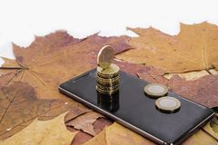 Smartphone on maple leaves background with some coins. Autumn abstraction royalty free stock photo