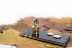 Smartphone on maple leaves background with some coins. Autumn abstraction stock photo