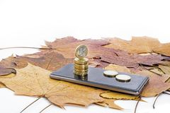 Smartphone on maple leaves background with some coins. Autumn abstraction stock photography