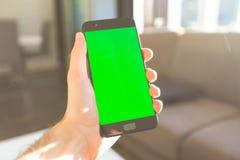 Smartphone maschio della tenuta della mano con dello schermo luce solare verde all'interno fotografie stock libere da diritti