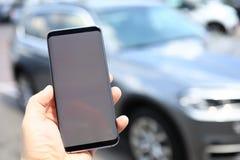 Smartphone masculino da posse da mão com placa fotografia de stock