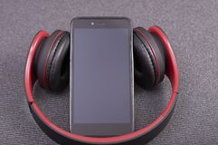 Smartphone med bluetoothhörlurar som lyssnar till musik arkivfoto