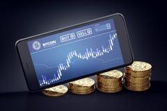 Smartphone med den Bitcoin diagrampå-skärmen som lägger på växande högar av guld- Bitcoins Royaltyfri Bild