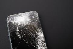 Smartphone med den brutna skärmen på mörk bakgrund Arkivfoto
