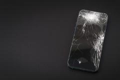 Smartphone med den brutna skärmen på mörk bakgrund Arkivbilder