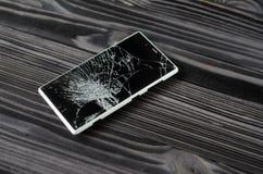 Smartphone med den brutna skärmen på mörk bakgrund royaltyfria foton