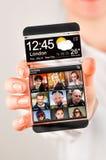 Smartphone med den genomskinliga skärmen i mänskliga händer. Arkivfoton