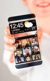 Smartphone med den genomskinliga skärmen i mänskliga händer. Arkivbilder