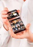 Smartphone med den genomskinliga skärmen i mänskliga händer. Arkivbild