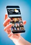 Smartphone med den genomskinliga skärmen i mänskliga händer. Royaltyfri Bild