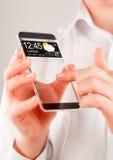 Smartphone med den genomskinliga skärmen i mänskliga händer Royaltyfria Bilder