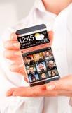 Smartphone med den genomskinliga skärmen i mänskliga händer Arkivbild