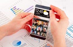 Smartphone med den genomskinliga skärmen i mänskliga händer Royaltyfri Bild