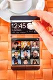 Smartphone med den genomskinliga skärmen i mänskliga händer Fotografering för Bildbyråer