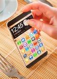 Smartphone med den genomskinliga skärmen i mänskliga händer Arkivbilder