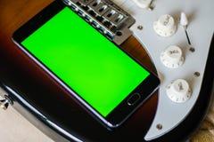 Smartphone med den gröna skärmen på en gitarr för elektriska gitarrer Arkivfoto