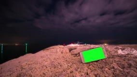 Smartphone med den gröna skärmen med timelapse i bakgrunden arkivfilmer