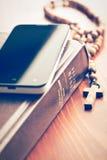 Smartphone med den heliga bibeln och radbandet Royaltyfri Foto