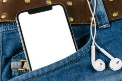 Smartphone med den isolerade vita skärmen i jeans stoppa i fickan med hörlurar Affärsarbetsplats med kopieringsutrymme Tomt avstå arkivfoton