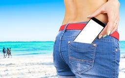 Smartphone med den isolerade vita skärmen med tomt utrymme för text i ett jeansfack av en ung härlig flicka, havbakgrund Arkivbild