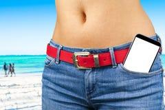 Smartphone med den isolerade vita skärmen med tomt utrymme för text i ett jeansfack av en ung spenslig flicka, havbakgrund Fotografering för Bildbyråer