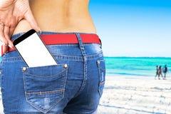 Smartphone med den isolerade vita skärmen med tomt utrymme för text i ett jeansfack av en ung härlig flicka, havbakgrund royaltyfria foton