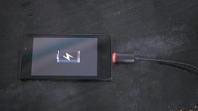 Smartphone med den låga batterisymbolen på skärmen Arkivbild