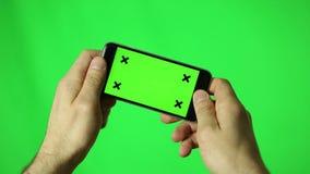 Smartphone med den manliga handdetaljen för grön skärm som spelar en lek i landskap lager videofilmer