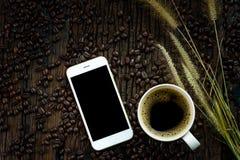 Smartphone med den svarta tomma skärmen, kaffekoppen, blommor för torrt gräs och grillade kaffebönor på trätexturbakgrund Fotografering för Bildbyråer
