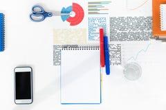 Smartphone med den tomma skärmen, den tomma anteckningsboken med markörer, sax och affärsdiagram på arbetsplatsen Arkivfoton