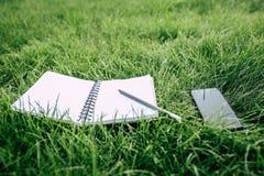 Smartphone med den tomma skärmen, den tomma anteckningsboken och blyertspennan på grönt gräs Royaltyfria Bilder