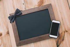 Smartphone med den tomma skärmen och den tomma fotoramen med flugan på trätabellöverkant Arkivbild