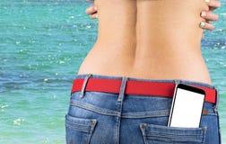 Smartphone med den vita skärmen med tomt utrymme för text i ett jeansfack av en ung spenslig flicka, havbakgrund Arkivbilder