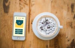 Smartphone med det nya meddelandet på skärmen och en kopp kaffe på Fotografering för Bildbyråer