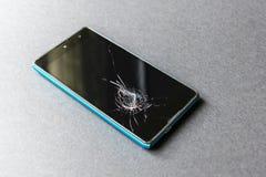 Smartphone med en bruten skärm på en mörk bakgrund closeup royaltyfri fotografi