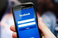 Smartphone med Facebook den sociala nätverksmobilen app Arkivbild