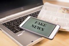 Smartphone med fejkar nyheternaord på skärmen över en tidning och en bärbar dator Fejka nyheterna, LURA begreppet royaltyfria foton