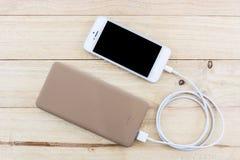 Smartphone med guld- powerbank Arkivfoton